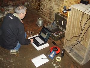 Serwis stacji sejsmicznej  i zgrywanie zarejestrowanych danych podczas eksperymentu sejsmicznego. Czujnik drgań (sejsmometr) umieszczony na betonowej posadzce w piwnicy budynku. (Źródło: IGF PAN)