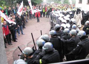 Policja otaczająca szczelnym kordonem taczkę z kukłą burmistrzyni